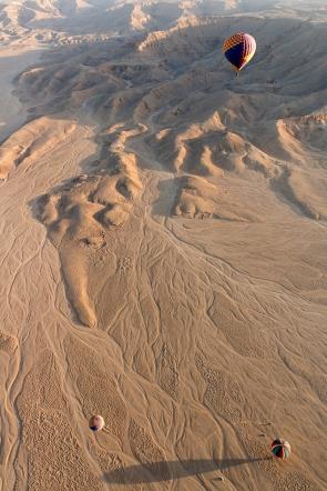 A couple of balloons landing in the desert