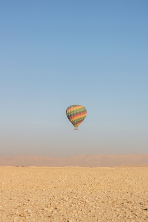 Another balloon coming in for a landing on the flat desert sand